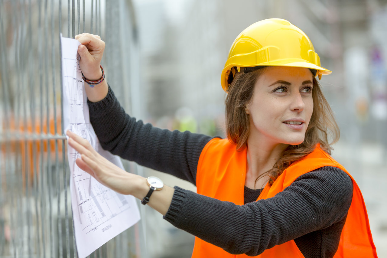 Portrait of woman architect at construction site holding office blueprints on scaffolding